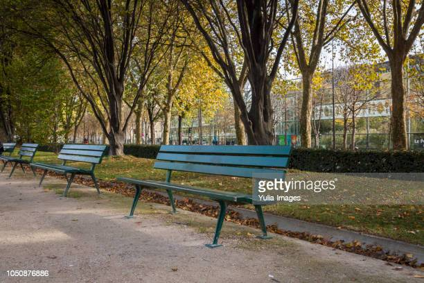 empty blue benches in park during autumn  paris  france - bench stock pictures, royalty-free photos & images