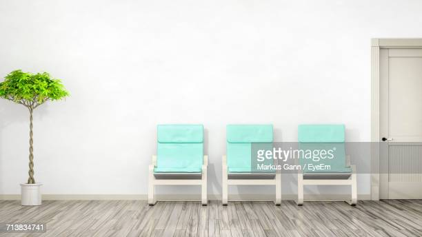Empty Blue Chairs On Floor Against White Wall
