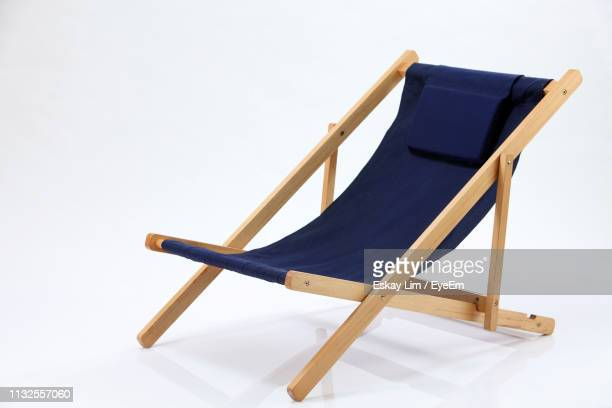 empty blue deck chair against white background - outdoor chair stock pictures, royalty-free photos & images