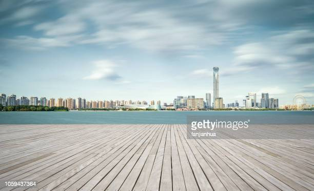 empty boardwalk by lakeside,urban skyline background,suzhou - boardwalk stock pictures, royalty-free photos & images