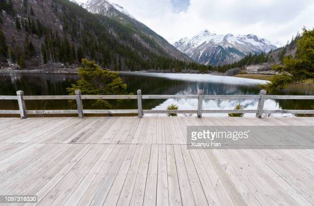 empty boardwalk with snow mountains - floorboard stock photos and pictures