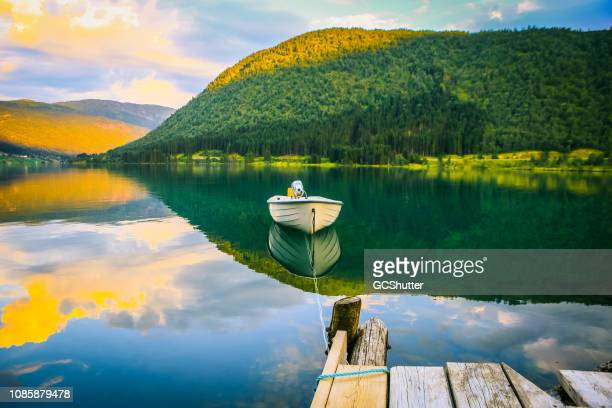 empty boat tied to the dock with a rope on the calm fjord - majestoso imagens e fotografias de stock