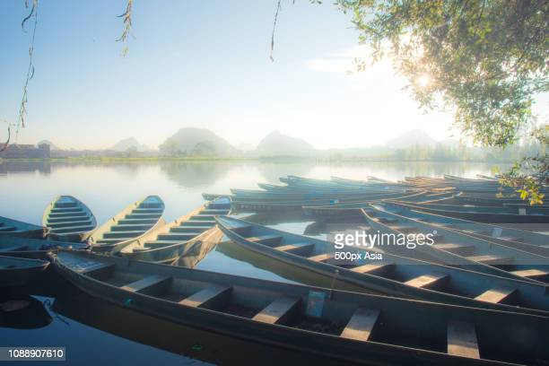 empty boats on shore of river, wenshan, yunnan, china - image stock pictures, royalty-free photos & images