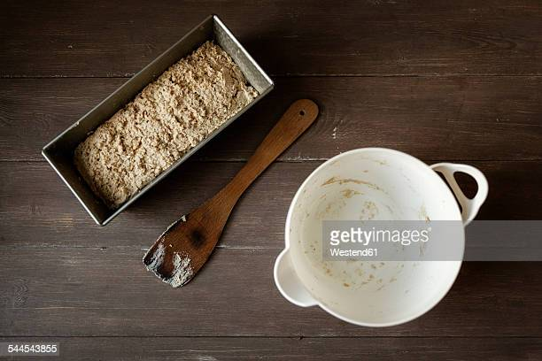 Empty bowl, scraper and baking pan with buckwheat bread dough on wood