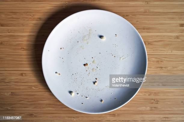 empty breakfast dish with bread crumbs on a bamboo wooden table - 残り物 ストックフォトと画像