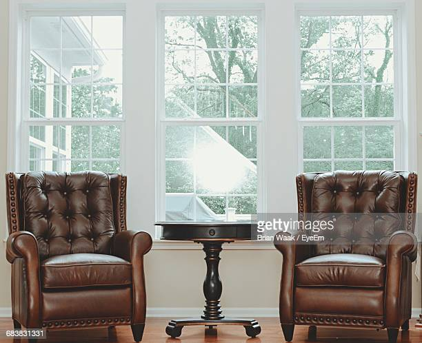 Empty Brown Leather Armchairs By Window At Home