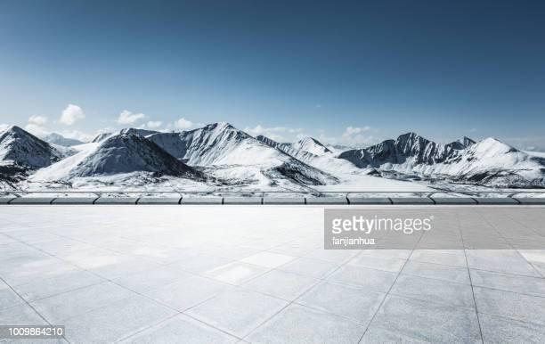 empty car park front of snow-capped mountains - front view photos et images de collection