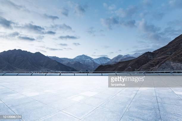 empty car park front of snow-capped mountains - hochplateau stock-fotos und bilder