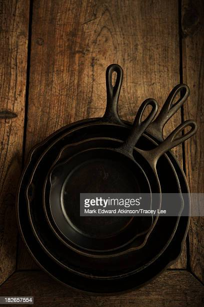 Empty cast iron pans on wooden board
