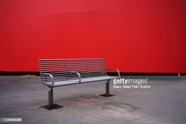 empty chair against red wall - klaus-dieter thill stock-fotos und bilder