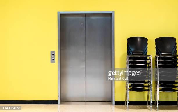 empty chair against yellow wall - elevador - fotografias e filmes do acervo