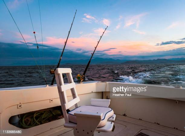 empty chair and fishing rods on moving boat at dawn - deep sea fishing stock photos and pictures