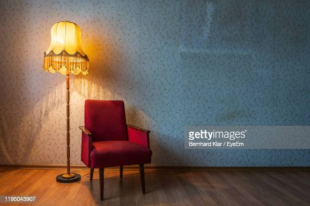 empty chair and lamp against wall at home - 肘掛け椅子 ストックフォトと画像