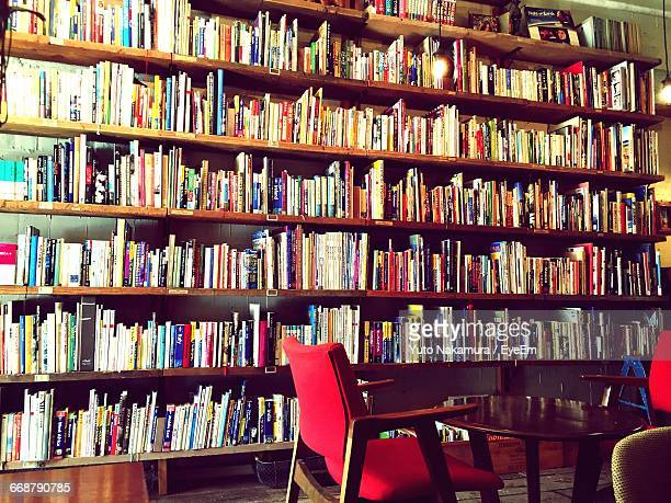 Empty Chair And Table Against Bookshelves In Library