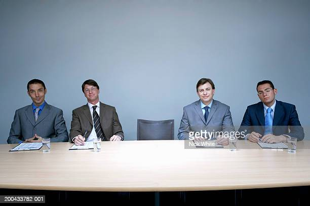 Empty chair at desk between four businessmen, one with eyes closed