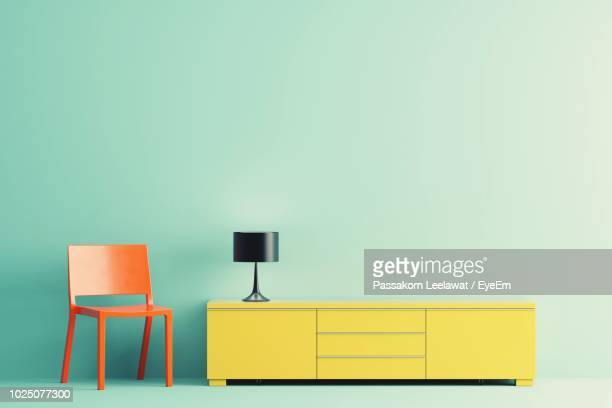 Empty Chair By Electric Lamp And Cabinet Against Colored Background