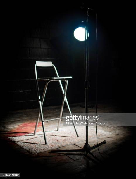 Empty Chair By Illuminated Light Equipment On Stage