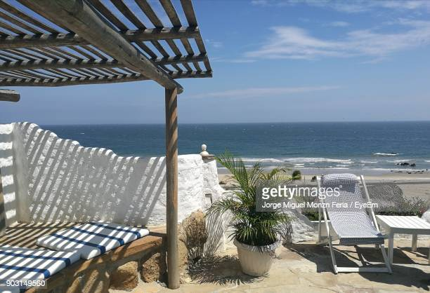 Empty Chair By Potted Plant Against Sea