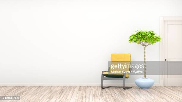 Empty Chair By Potted Plant Against Wall At Home