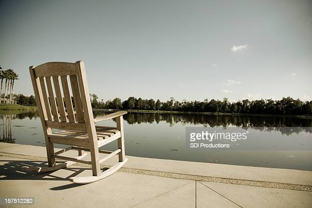 empty chair on a florida lake - rocking chair stock photos and pictures