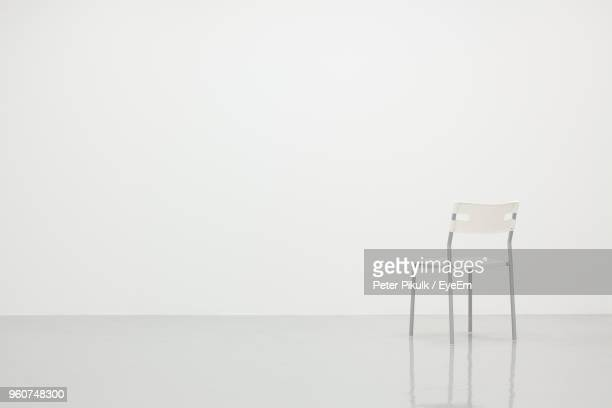 empty chair on floor against white background - copy space stockfoto's en -beelden