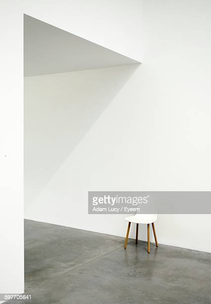 Empty Chair On Floor Against White Wall