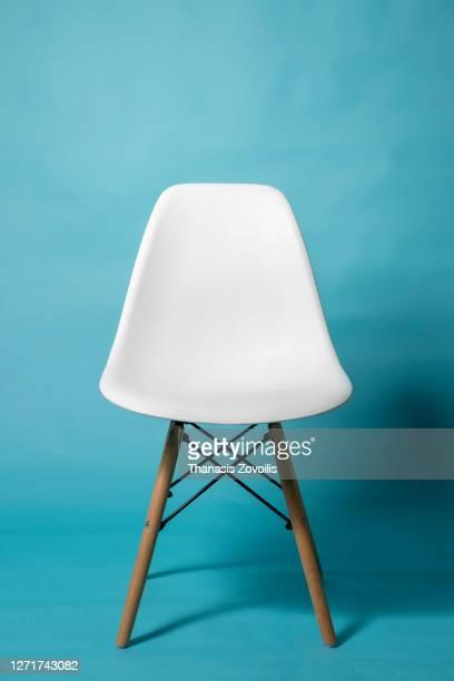 empty chair taken in studio with blue background - stuhl stock-fotos und bilder