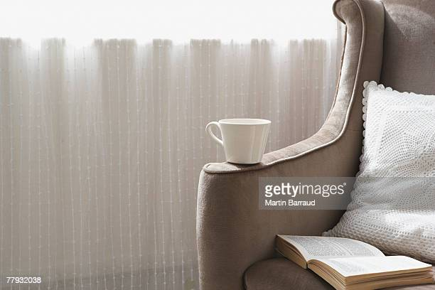 empty chair with book open and mug on arm - cushion stock photos and pictures