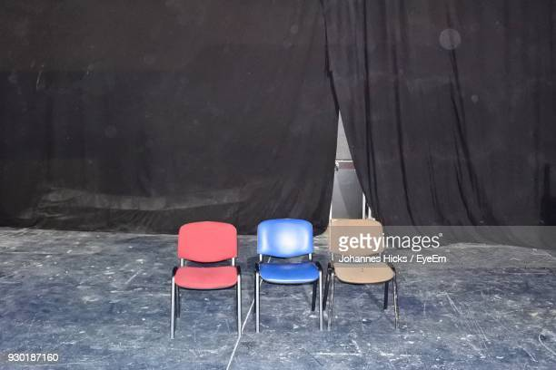 Empty Chairs Against Black Curtain