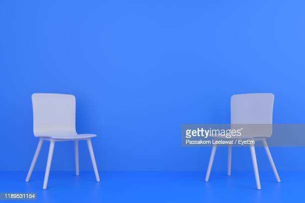 empty chairs against blue background - chair stock pictures, royalty-free photos & images