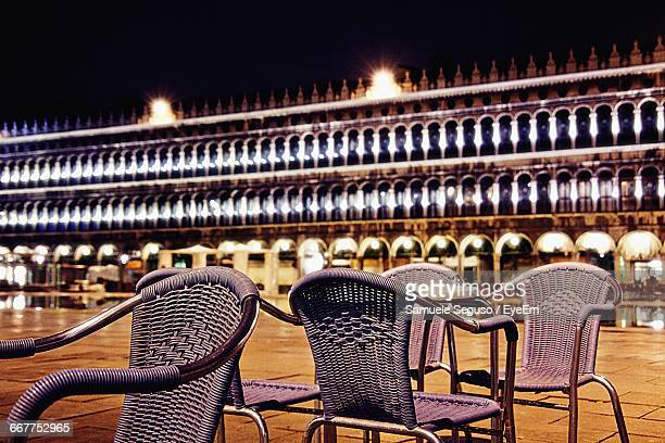 Empty Chairs Against Illuminated Doges Palace At St Marks Square