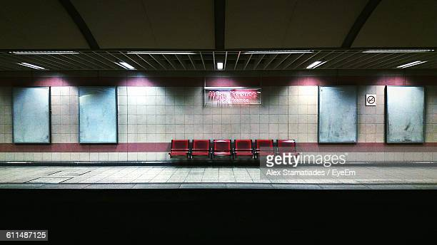 Empty Chairs Against Illuminated Wall At Subway Station