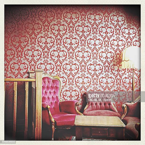 Empty Chairs Against Patterned Wall In Restaurant