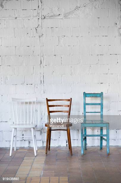 empty chairs against white brick wall - chair stock pictures, royalty-free photos & images