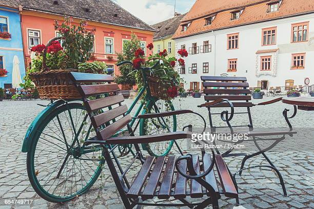 empty chairs and bicycle on street against buildings - lutai razvan stock pictures, royalty-free photos & images