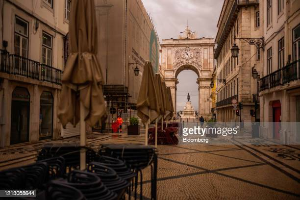 Empty chairs and collapsed sun parasols stand stacked along Rua Augusta outside closed restaurants and cafes in Lisbon, Portugal on Thursday, May 14,...