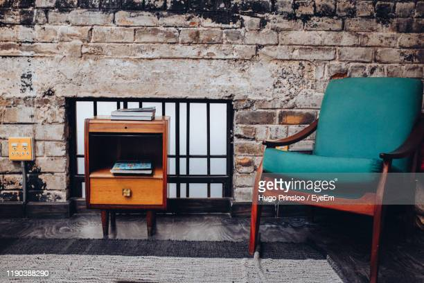 empty chairs and table against wall at home - prinsloo photos et images de collection