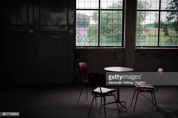 Empty Chairs And Table Against Window