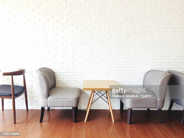 empty chairs and table by white wall at restaurant - floorboard stock photos and pictures