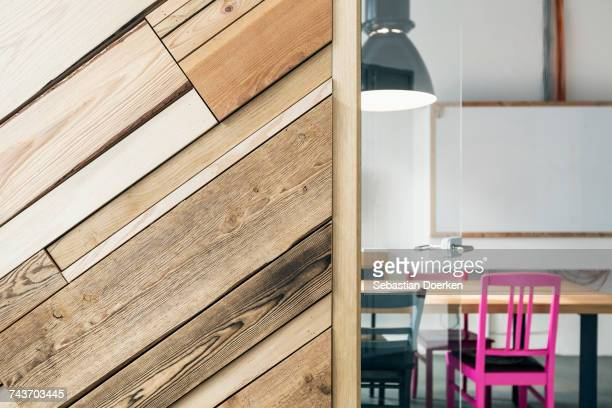 Empty chairs and table seen through doorway by wooden wall