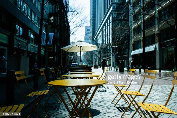 empty chairs and tables at cafe in city - オープンカフェ ストックフォトと画像