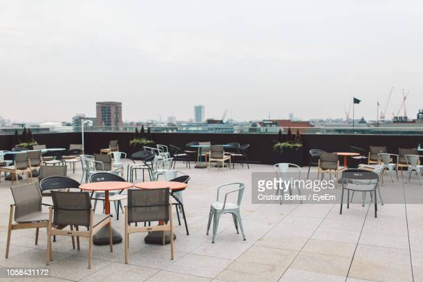 empty chairs and tables at outdoor cafe in city - bortes foto e immagini stock