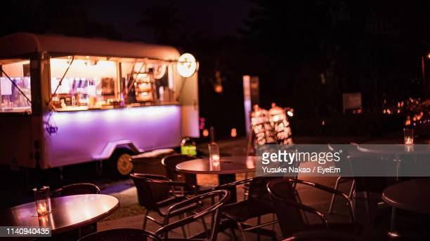 empty chairs and tables at outdoor cafe in illuminated city at night - food truck photos et images de collection