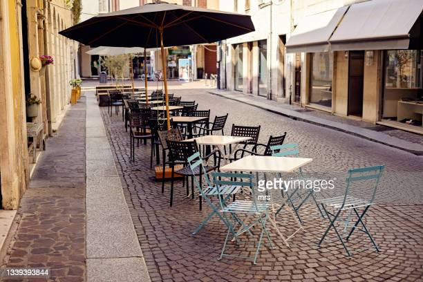 empty chairs and tables at sidewalk cafe - mantua stock pictures, royalty-free photos & images