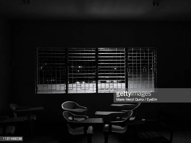 empty chairs and tables in darkroom at night - 単色画 ストックフォトと画像