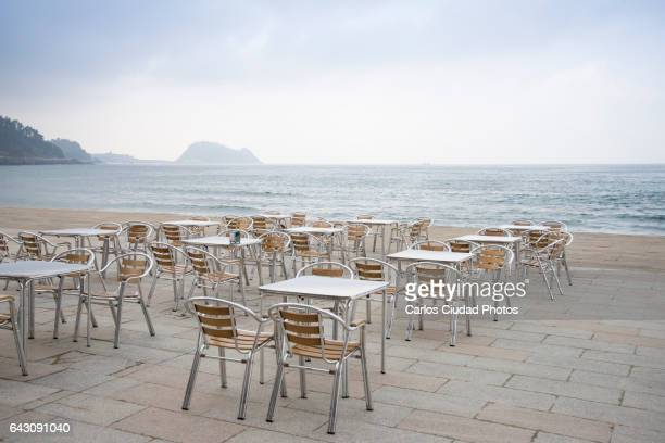 Empty chairs and tables in front of the Cantabrian sea, Zarautz, Basque Country