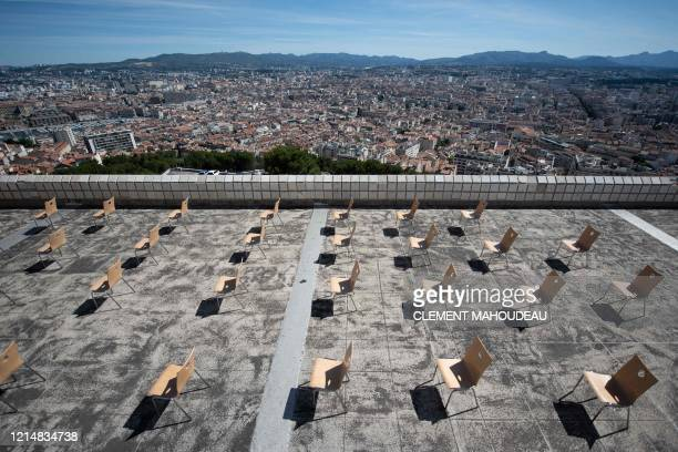 Empty chairs are disposed so worshippers can observe social distancing measures on Notre Dame de la Garde Basilica's terrace in Marseille southern...