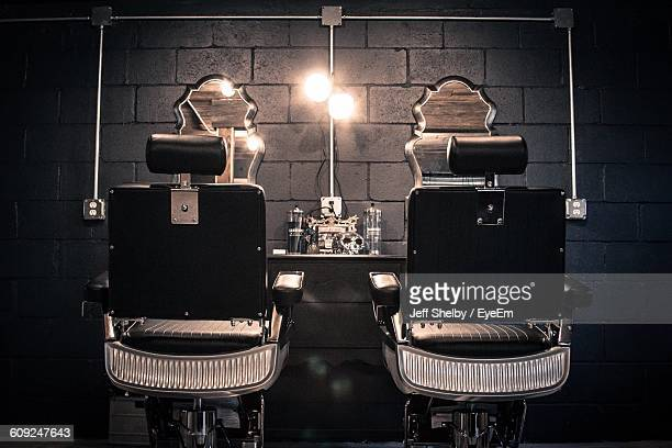 empty chairs at illuminated barber shop - barber shop stock photos and pictures