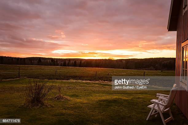 Empty Chairs By House Against Cloudy Sky During Sunset