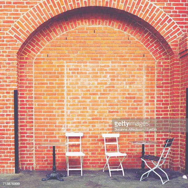 Empty Chairs By Table Against Brick Wall At Cafe
